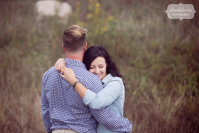 Happy photo of couple hugging during engagement photo shoot at the Coolidge Reservation.
