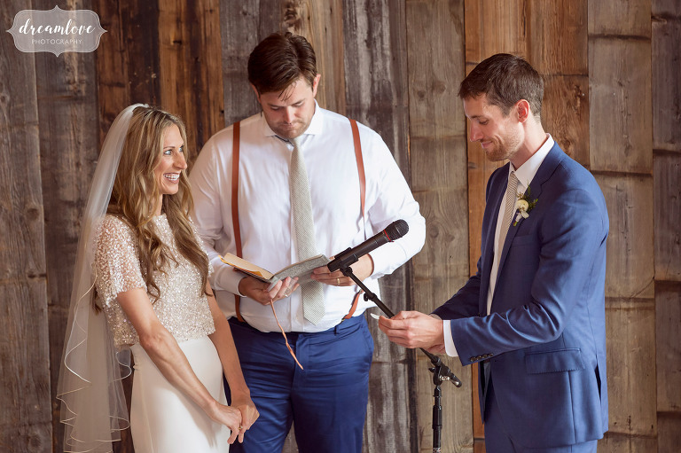 Natural wedding photography of the bride and groom exchanging vows during their barn ceremony in Stowe.