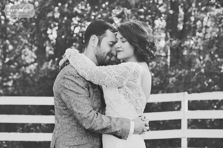 Black and white wedding photo of the bride and groom embracing in a horse pasture at the Barn at Liberty Farms in Ghent, NY.