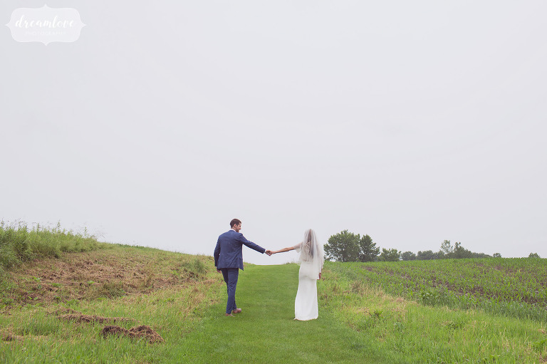 The bride and groom walk along the Stowe Quiet Path in the rain after their barn ceremony.