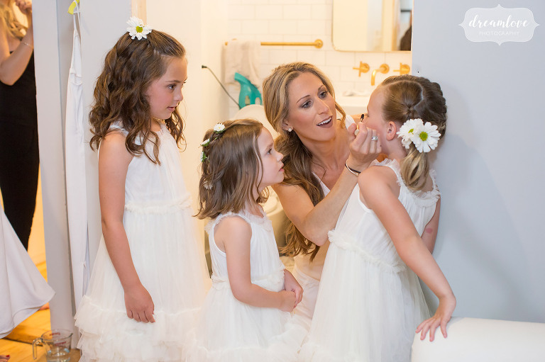 Documentary wedding photo of the bride helping her flower girls put on makeup before her Stowe, VT wedding.