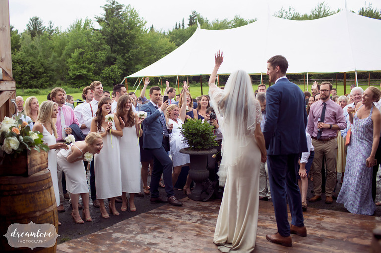 Bride and groom wave to guests at their Comfort Farm wedding in Stowe.