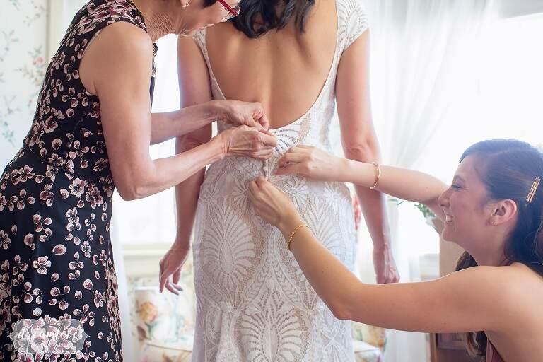 Bride's BHLDN Ludlow modern dress is buttoned up at Lyman Estate near Boston, MA.