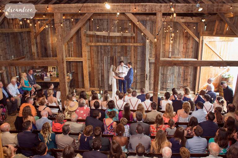 Here is an overall view of the inside of the Comfort Farm barn in Stowe during a wedding ceremony with a large guest list.
