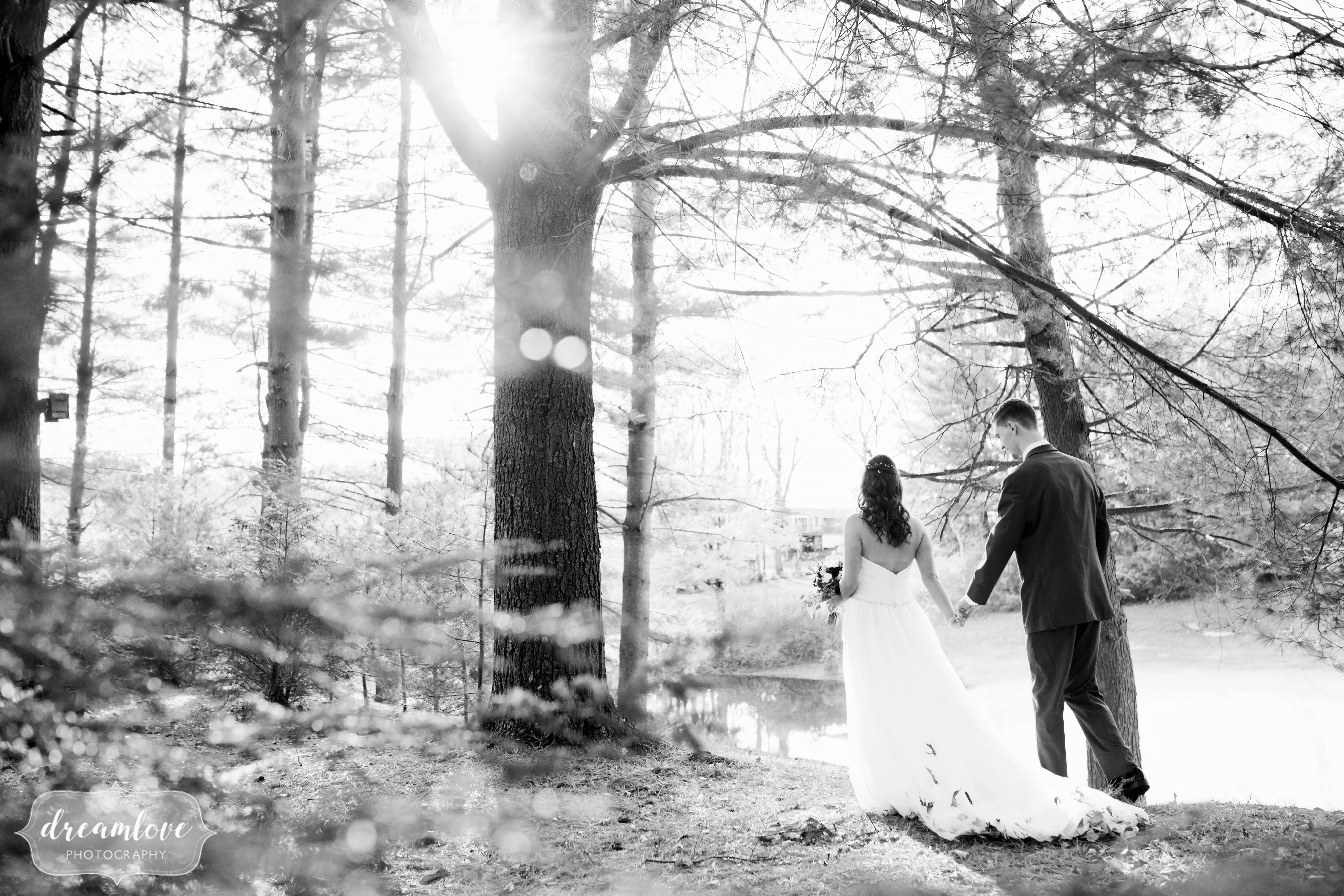Black and white wedding photography of the bride and groom walking through the woods at the Pavilion on Crystal Lake.