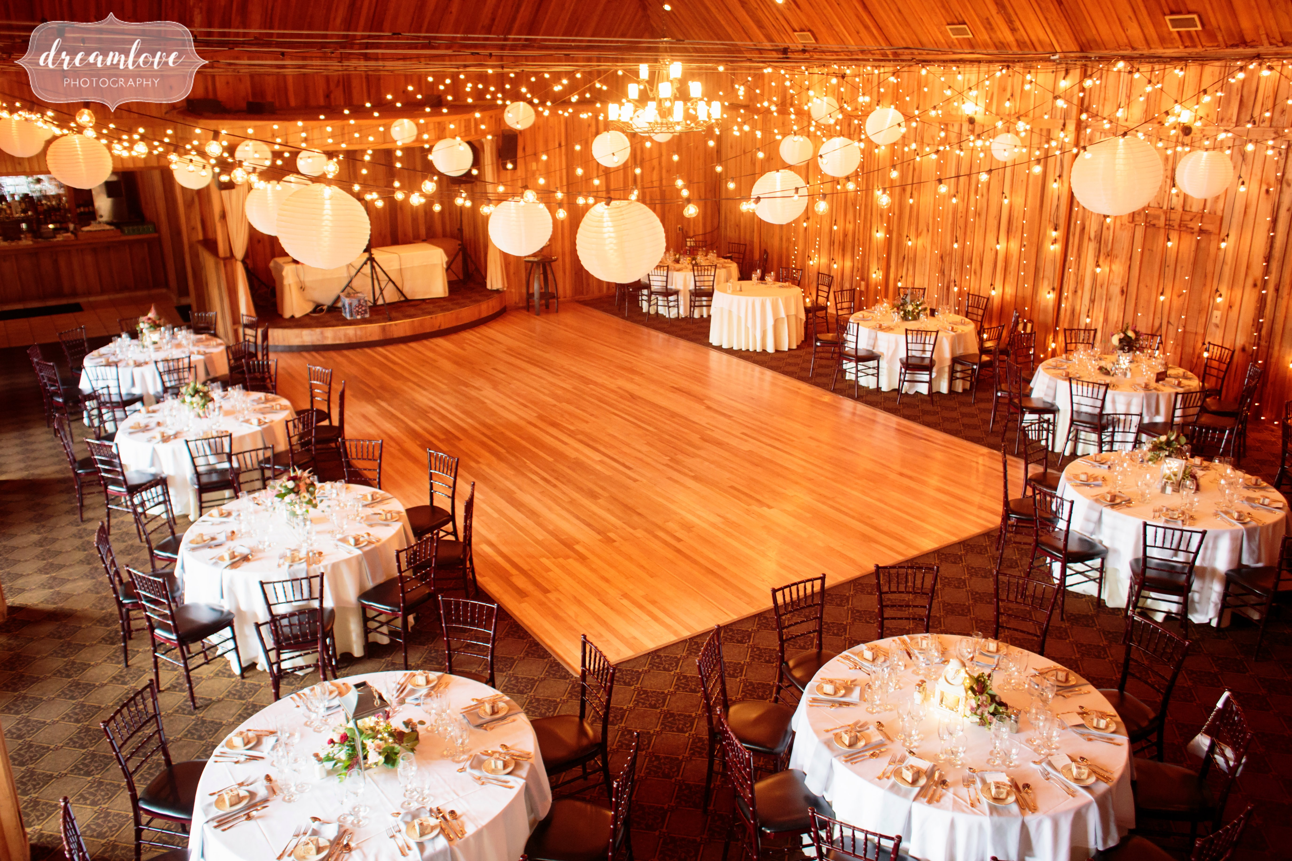 An inside view of the Pavilion on Crystal Lake with dance floor and round dinner tables set up.