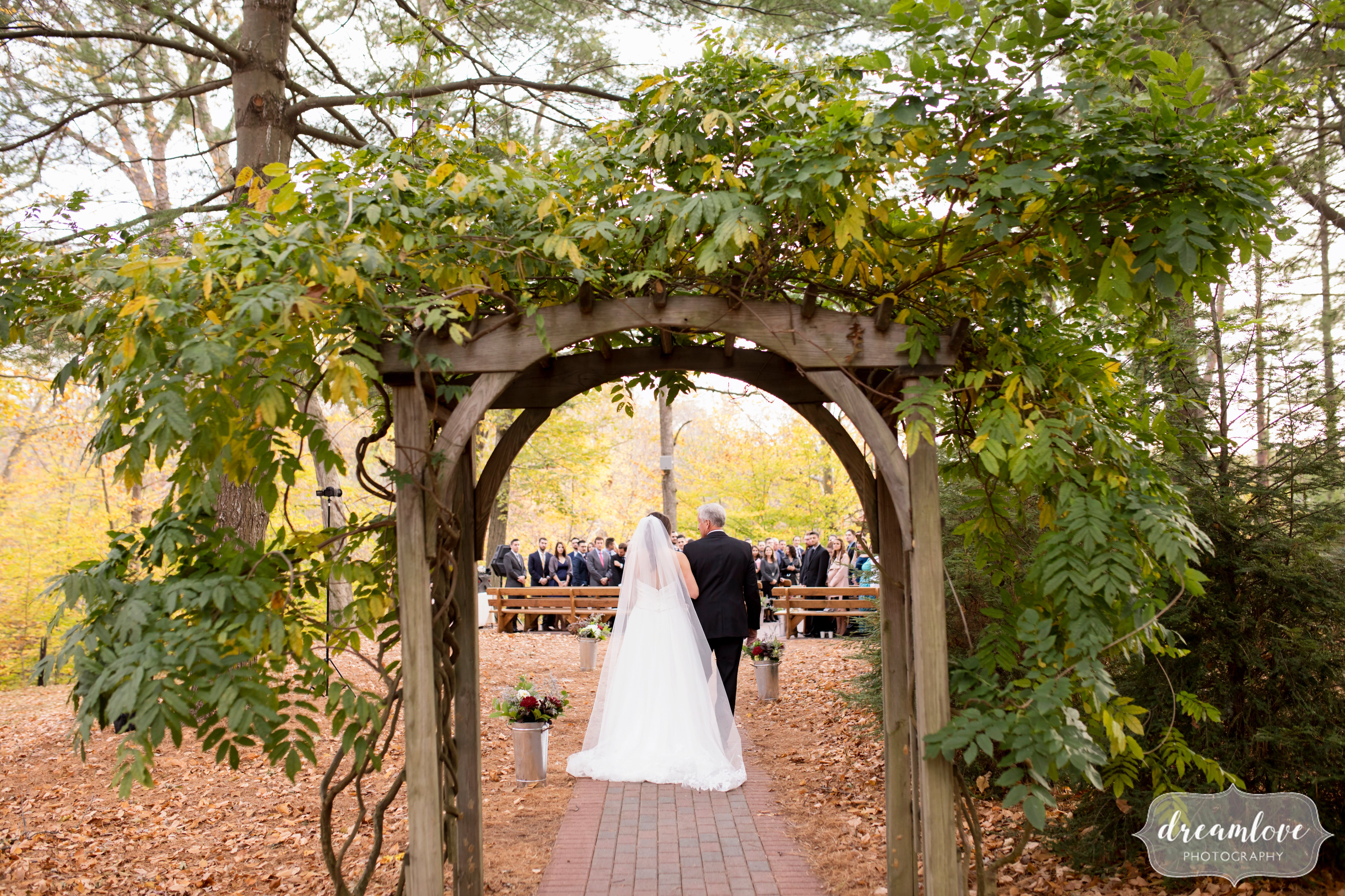 Bride and her father walk through an ivy covered arbor at the Crystal Lake Pavilion ceremony.