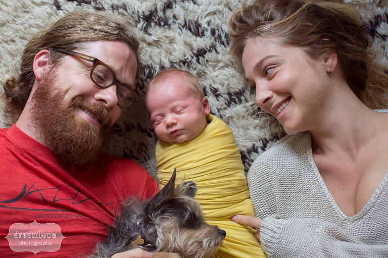 Natural and relaxed family photo of parents with newborn and dog in Venice, CA.