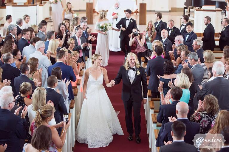 Bride and groom walk out of Rooke Chapel in central PA.