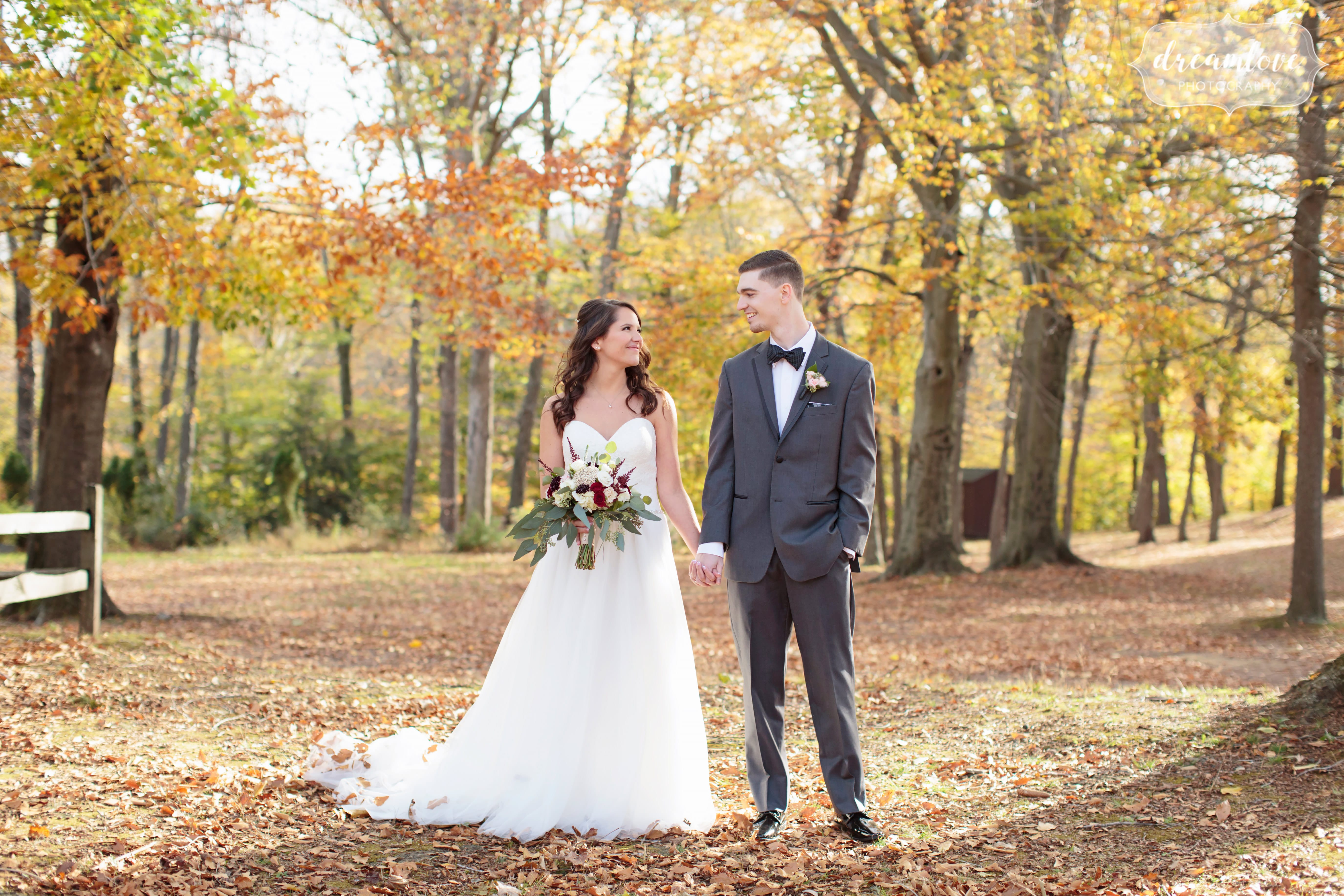Bride and groom holding hands under a canopy of yellow fall trees in CT.