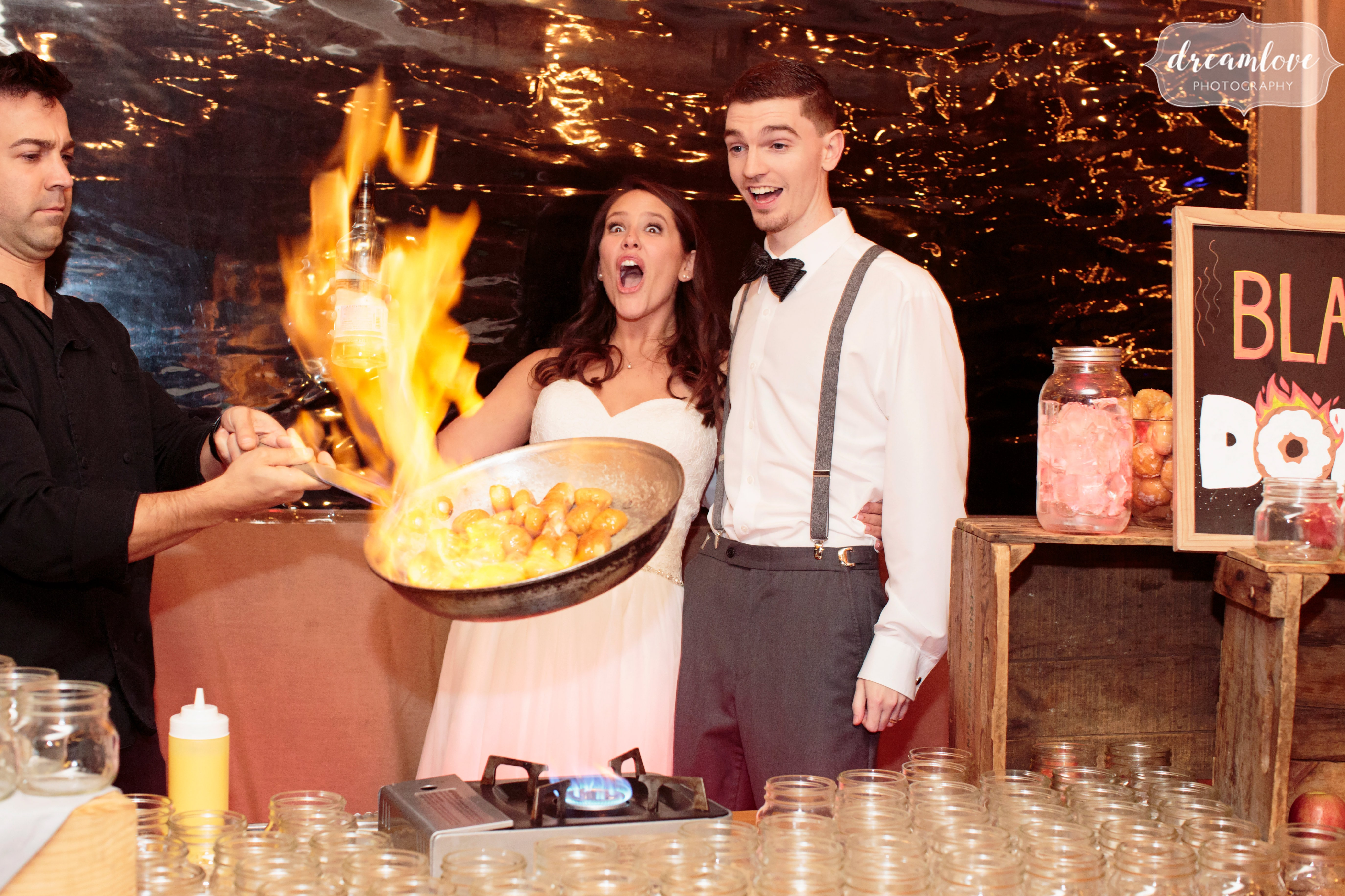 The bride is surprised when a pan catches on fire while frying doughnuts at her rustic wedding reception on Crystal Lake Pavilion.