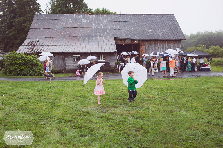 Kids holding umbrellas in front of the Stowe Comfort Farm on a rainy wedding day.