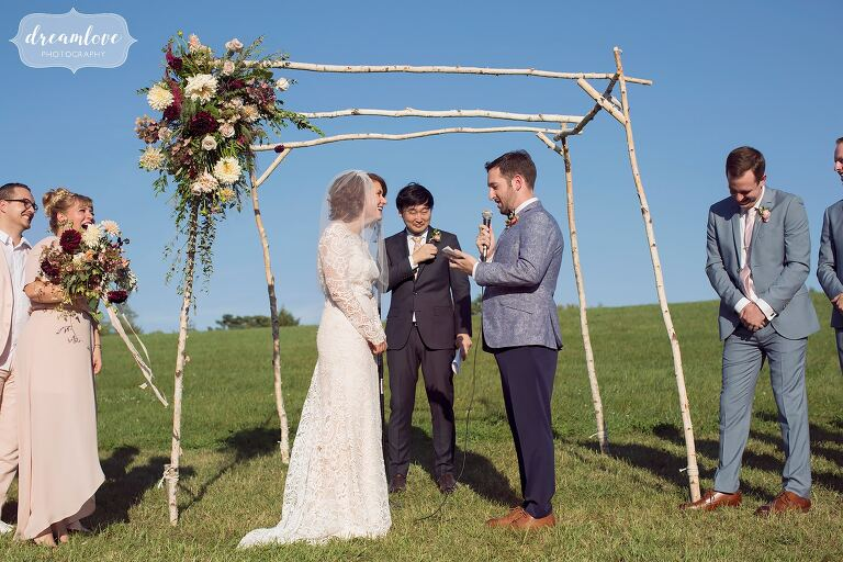 The groom reads his vows to the bride during their September wedding under a birch wood chuppah with flowerkraut flowers.