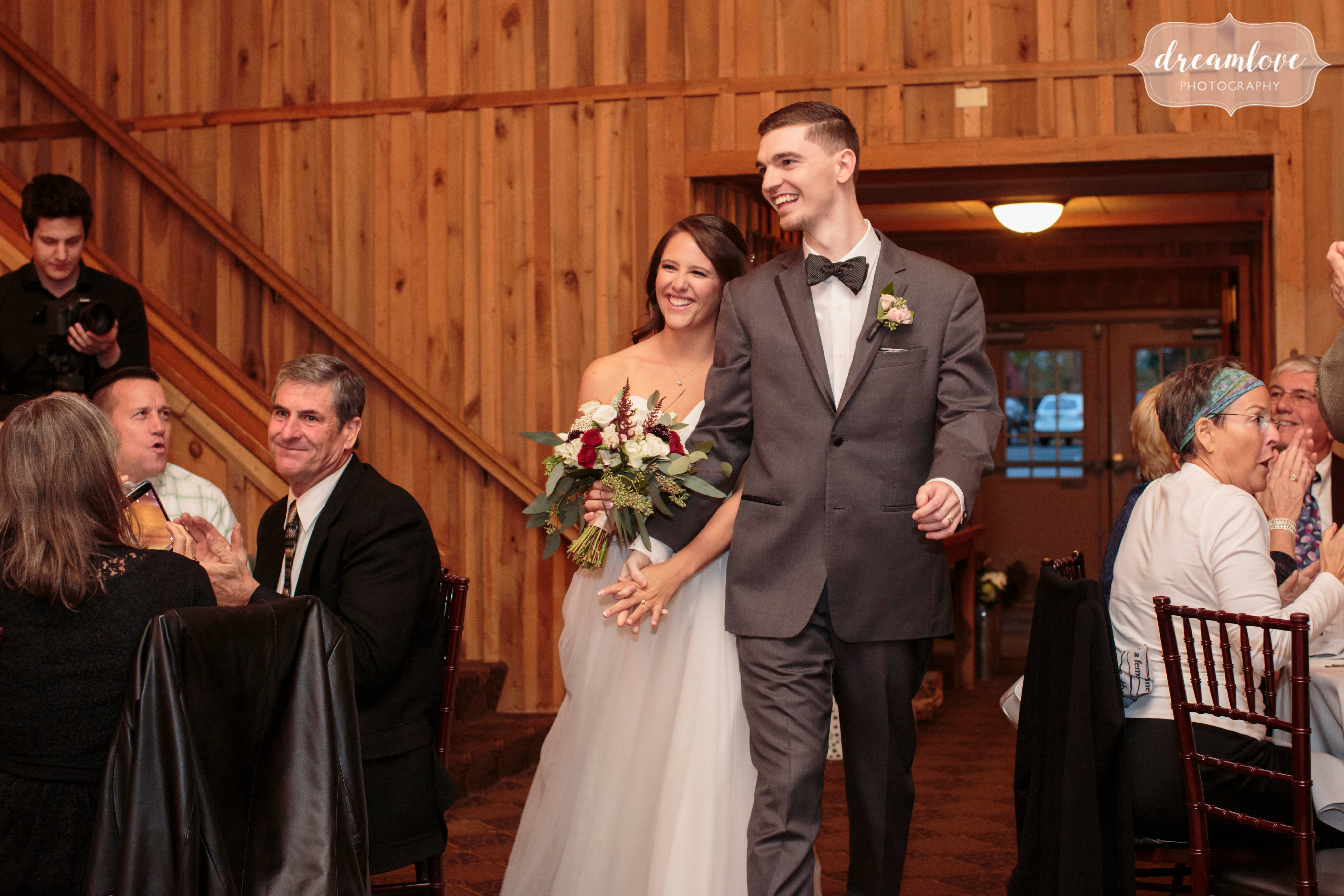 The bride and groom enter the rustic barn at the Crystal Lake Pavilion venue in CT.