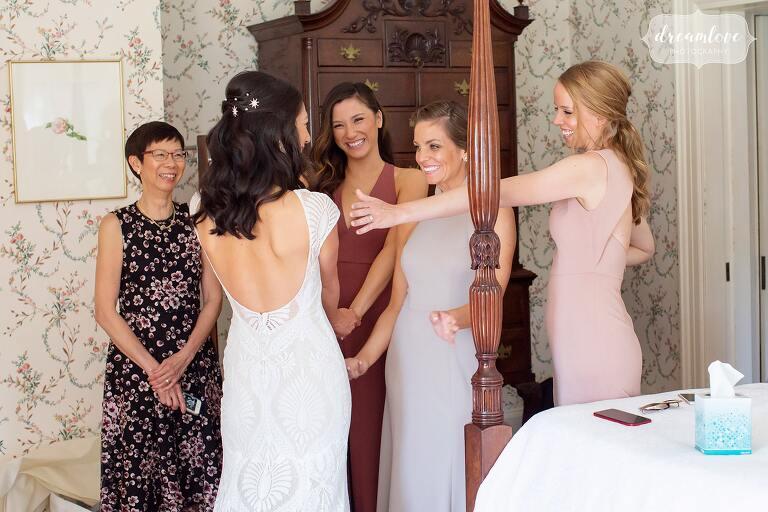 Bridesmaids hug bride at Lyman Estate.