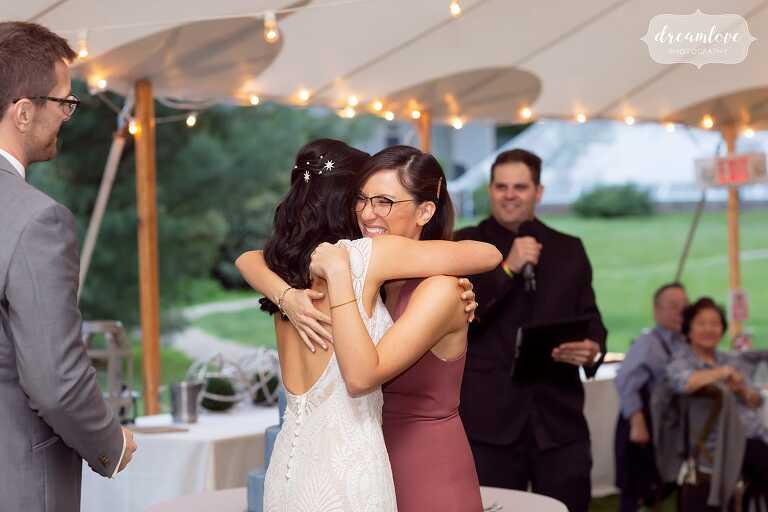 Bride and her sister hug after toast at Lyman Estate.