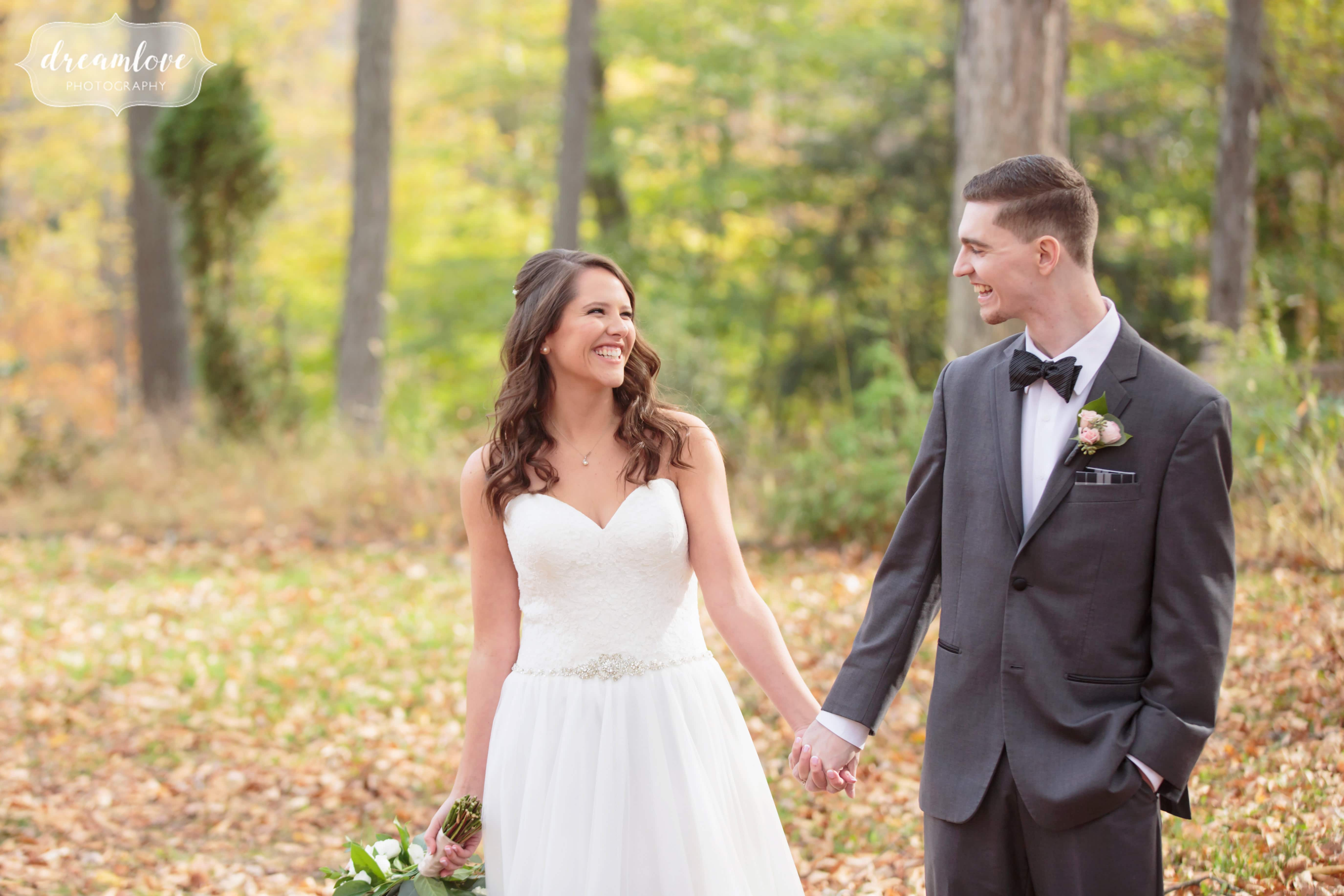 Romantic wedding photography of the bride and groom holding hands in the woods at the Pavilion on Crystal Lake outdoor venue in CT.
