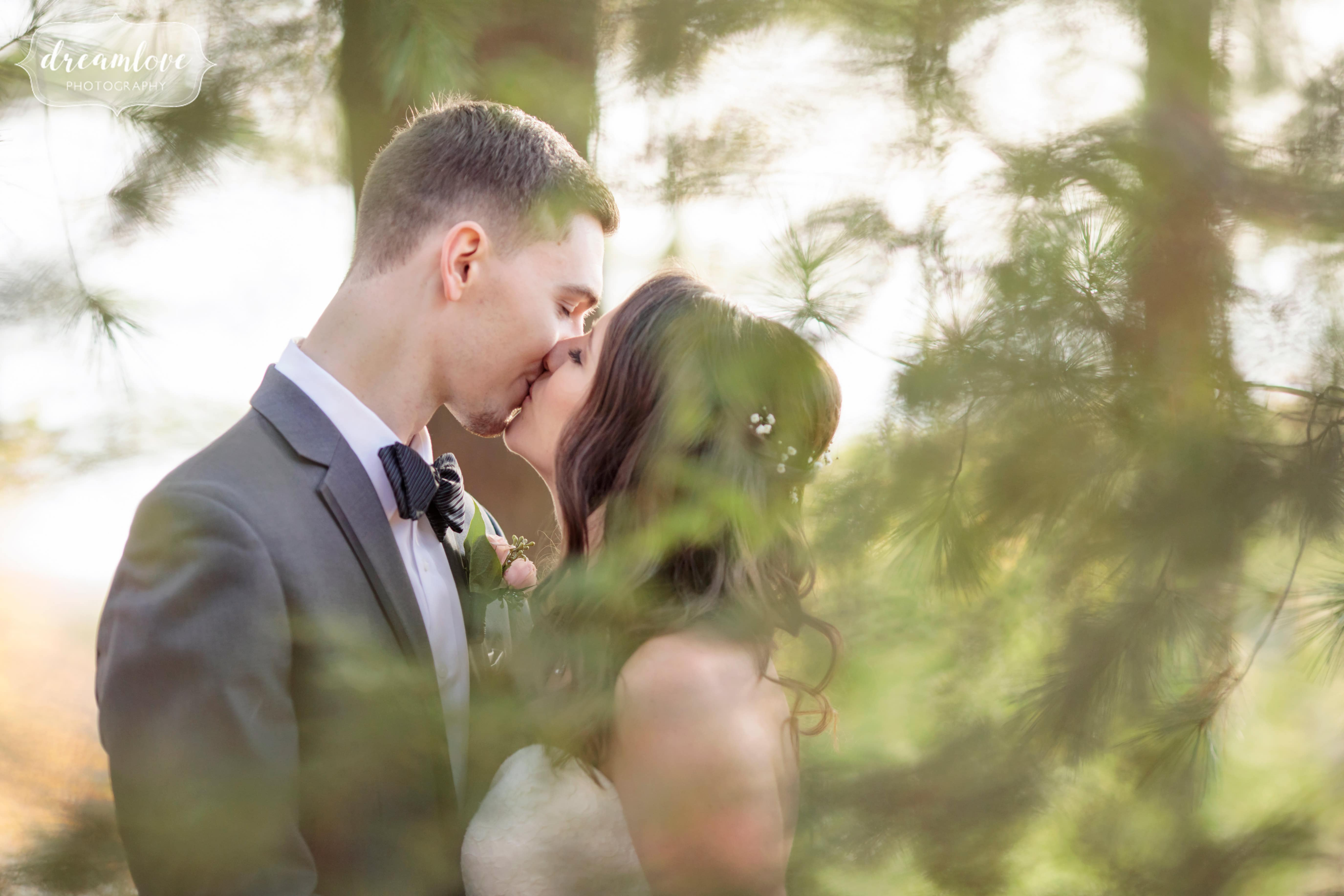 The bride and groom kissing under pine trees at the Crystal Lake Pavilion wedding venue.