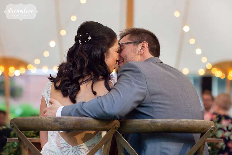 Sexy photo of bride and groom almost kissing under the tent with cafe lights at Boston wedding.