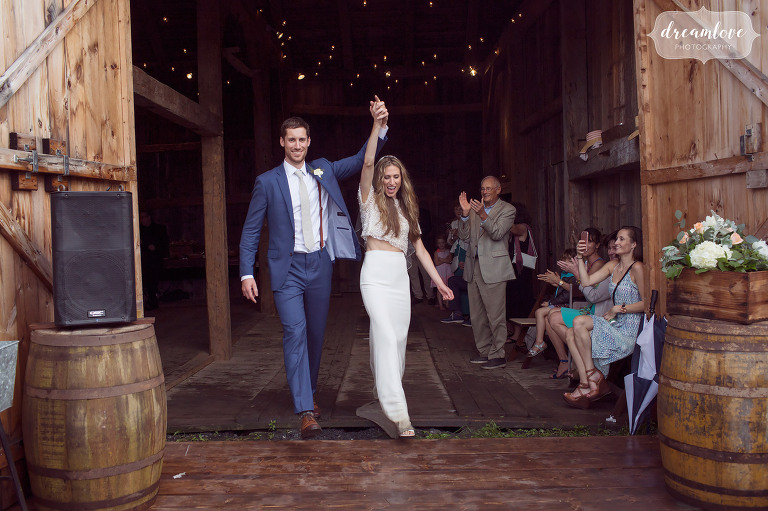 The beautiful bride and groom have their first dance in the rain at this Stowe, VT barn wedding.