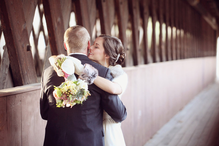 Winter wedding pictures of a bride and groom on a covered bridge in Woodstock, Vermont.