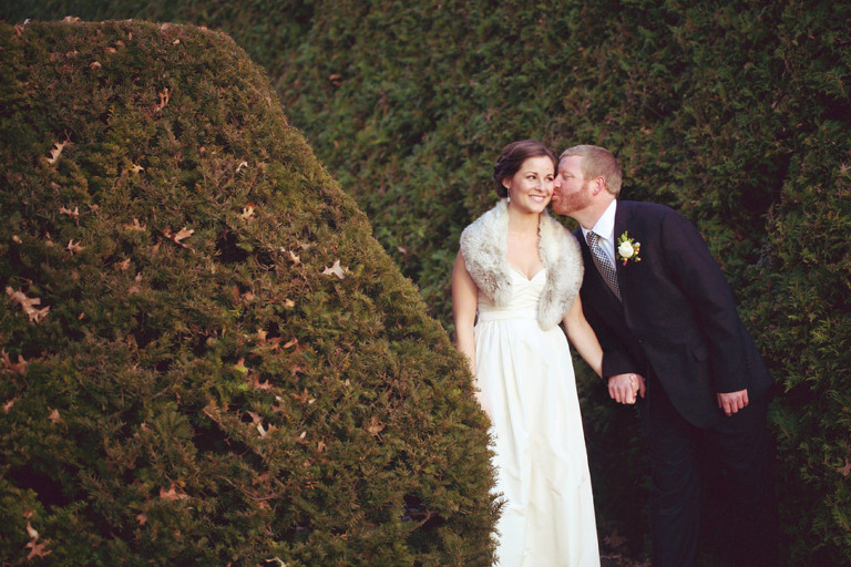 A groom leans over to kiss his bride on their wedding day at the Woodstock Inn.