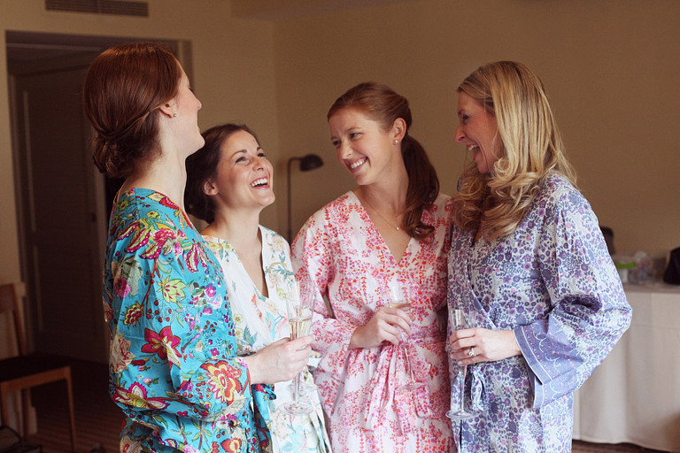 Bridesmaids laugh while drinking champagne and wearing complimentary colored jewel toned robes.