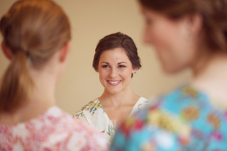 A bride smiles at her bridesmaids while getting ready for her wedding at the Woodstock Inn in Woodstock, VT.