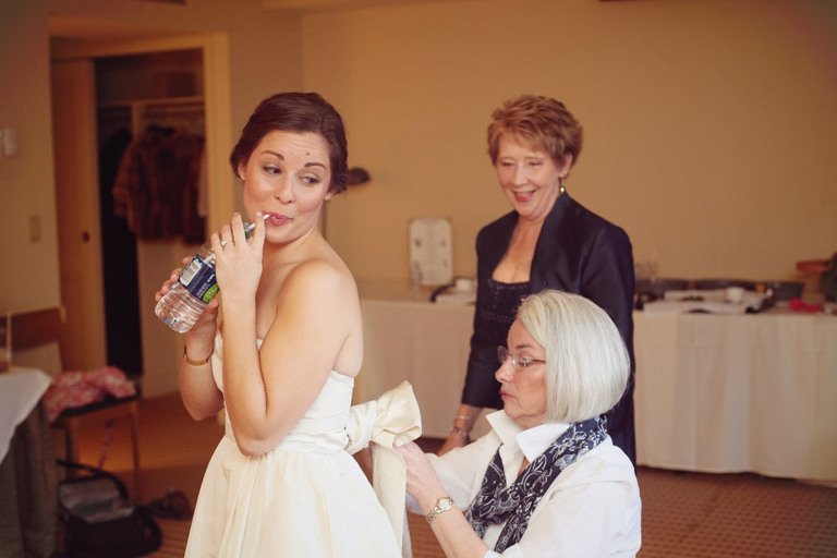 Mother of the bride helps her tie on a bow before getting married at the Woodstock Inn.