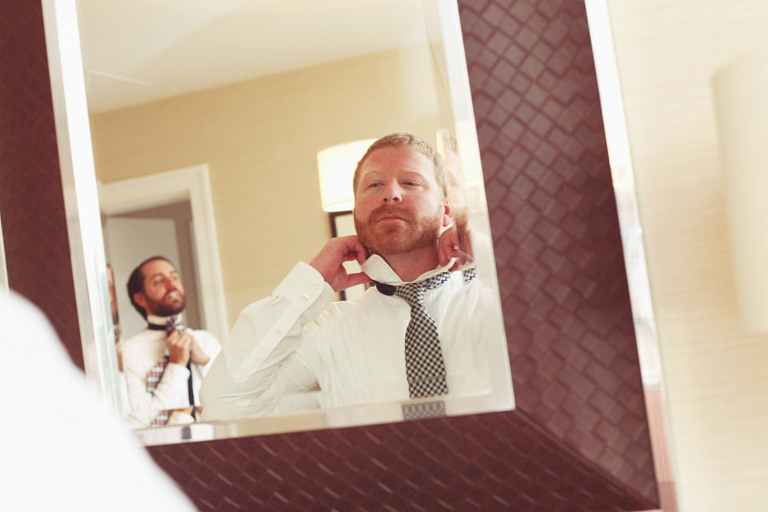 A groom fixes his collar and tie while getting ready for his wedding at the Woodstock Inn.