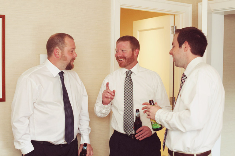 Groomsmen laugh while getting ready and drinking beer before a wedding.