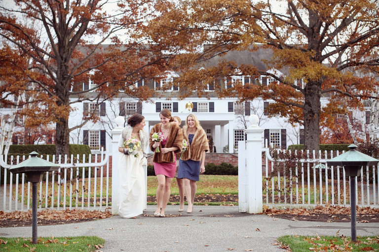 A laughing bride walks with her bridesmaids out in front of the Woodstock Inn in Vermont.