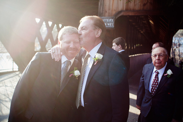 Father of the groom gives his son a kiss before a wedding in Woodstock, VT.