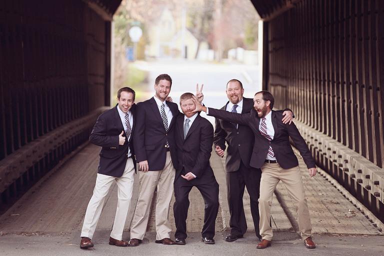 A goofy groomsmen pose idea at a covered bridge!