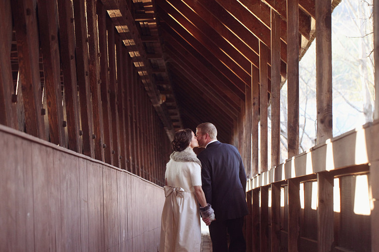 A bride and groom kiss while walking along the side of a covered bridge in Woodstock Vermont.
