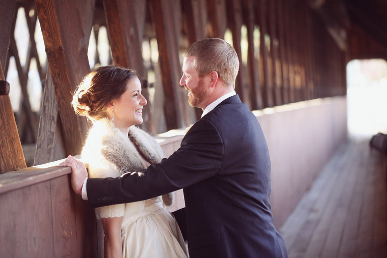 A bride and groom laugh while taking wedding pictures at an old covered bridge.
