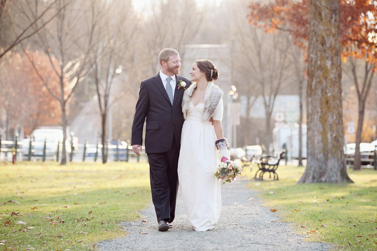 A bride and groom walk along the center path of the village green in Woodstock Vermont prior to their Woodstock Inn Winter wedding.