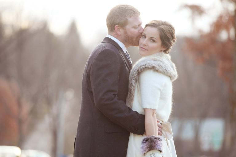 Groom kisses bride while taking winter wedding photos on the Woodstock, VT Village Green.