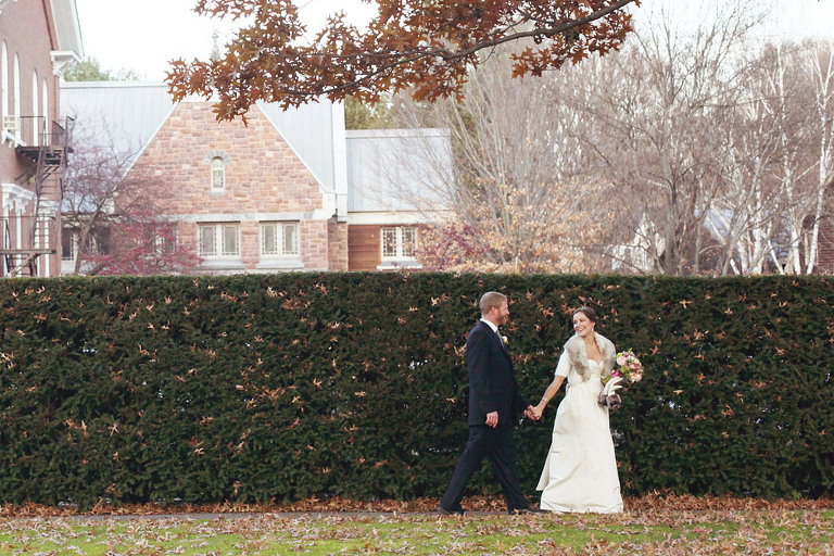 Bride and groom holding hands and smiling in downtown Woodstock, Vermont.