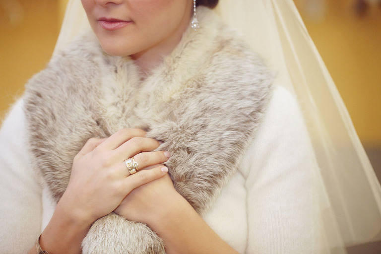 Detail of brides engagement ring and fur shawl.