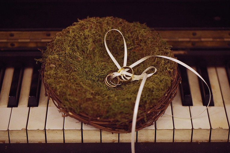 Wedding bands in a natural moss sitting on top of an antique piano.