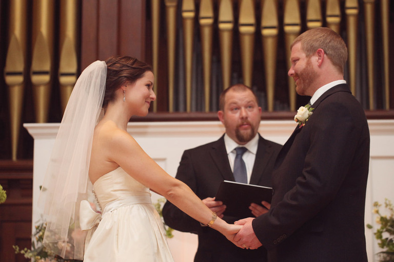 Bride and groom smile at each other during their wedding ceremony in Woodstock.