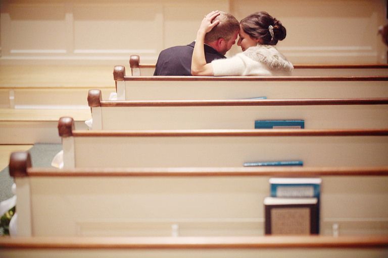 Bride and groom share a sweet moment in the pews at the North Universalist Chapel.