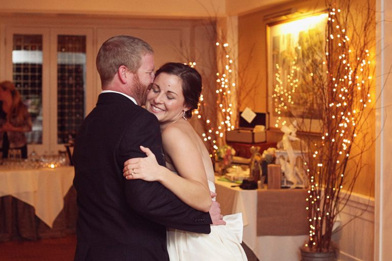 A bride and groom share a first dance surrounded by warm twinkle lights in the Rockefeller Room at the Woodstock Inn.