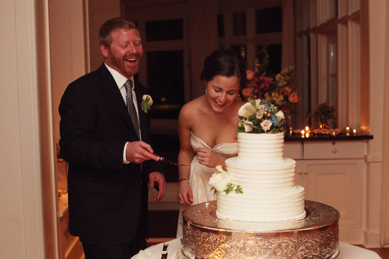 Bride and groom cut the cake at their wedding reception in the Rockefeller Room at the Woodstock Inn.