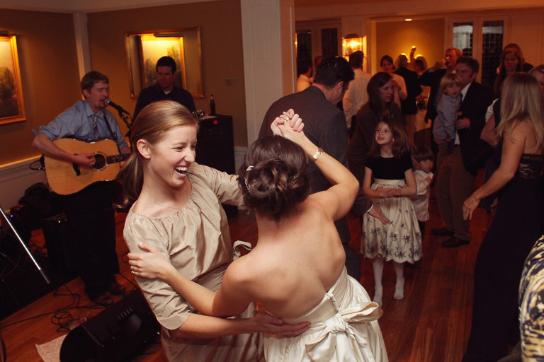 A bridesmaid and bride dance together to live music in Rockefeller Room at the Woodstock Inn.