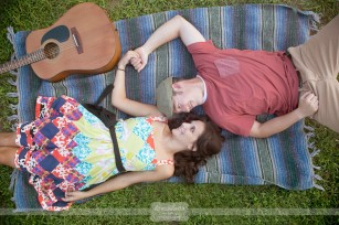 Engagement photo of a couple laying on a blanket with a guitar in the grass in NH.