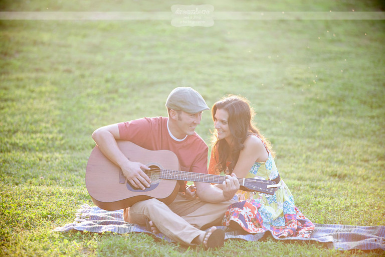 Engagement photo of guy playing guitar to girl while they sit on a blanket in the grass in NH.