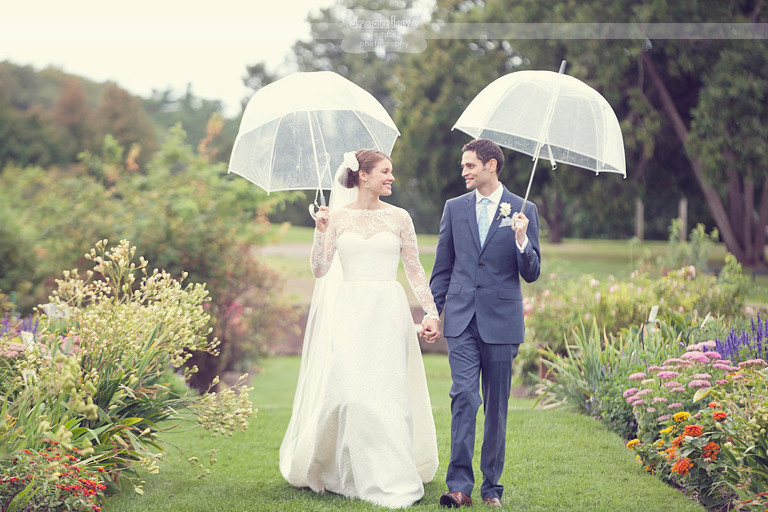 Bride and groom walk hand in hand while holding umbrellas at their Shelburne Farms wedding in Vermont.