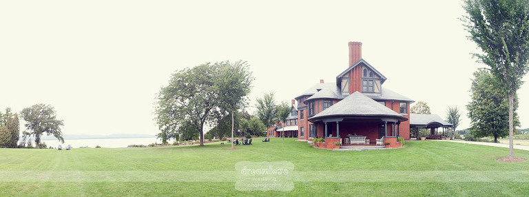 Scenic panorama of a Victorian house next to Lake Champlain at Shelburne Farms in Vermont.